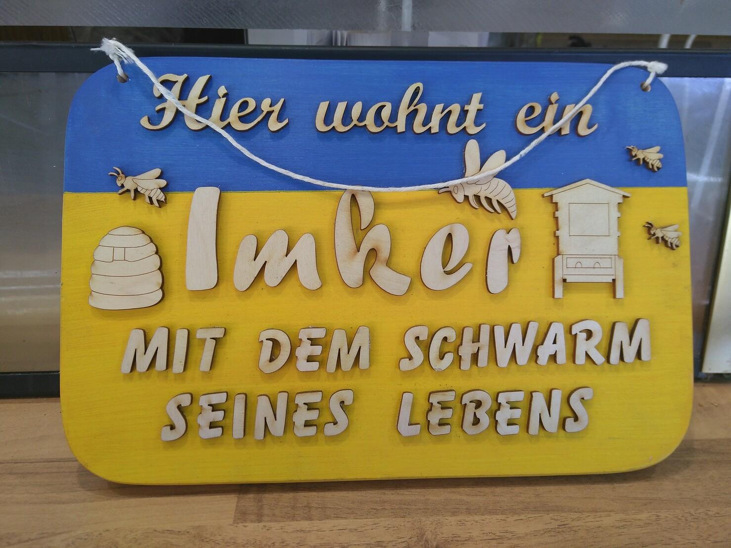 Ein Schild. Es ist oben blau, unten gelb. Darauf steht: Hier wohnt ein Imker mit dem Schwarm seines Lebens. Zu sehen sind außerdem ein Bienenstock (rund) und ein Kasten und umherfliegende Bienen
