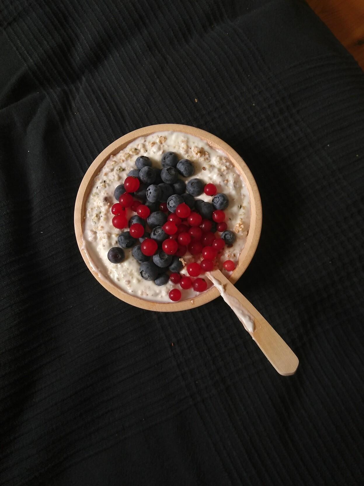 Eine Schüssel aus hellem Holz. Darin Schafjoghurt mit Blaubeeren und roten Johannisbeeren drauf und einem Holzlöffel der in dem Joghurt steckt